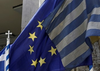 Greek national flags fly alongside a European Union (EU) flag, center, outside a store in Athens, Greece, on Monday, May 11, 2015. Finance chiefs meeting in Brussels on Monday will issue a statement to endorse Greece's work on a plan to fix up its economy, the officials said, asking not to be named because the talks were private. Photographer: Kostas Tsironis/Bloomberg